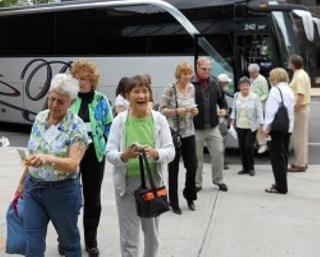 Elders getting off of travel bus